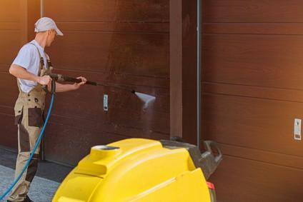 Garage Door Washing by High Pressured Water. Caucasian Men Cleaning Garage Doors.